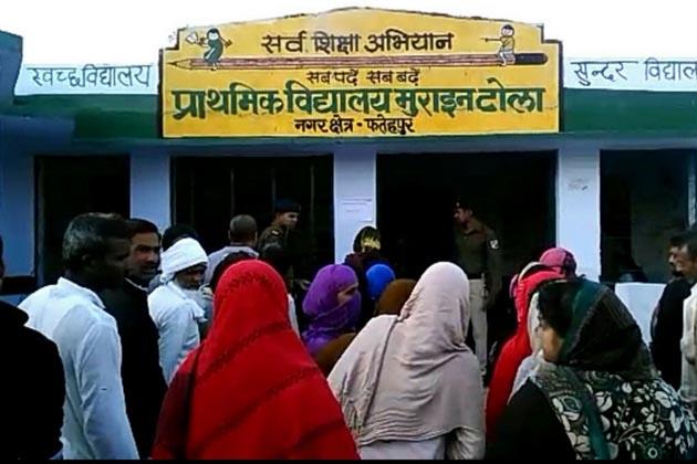 فتح پور نگر علاقے میں مرائن ٹولا میں بنے پولنگ بوتھ کے باہر ووٹ ڈالنے کے لئے انتظار کرتے لوگ۔