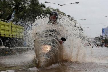جکارتہ کے ایک سیلاب زدہ علاقہ میں ایک شخص موٹر سائیکل چلاتے ہوئے۔ تصویر۔ رائٹرز۔