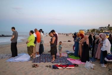 امریکہ کے نیو جرسی میں ایک بیچ پر عید کی نماز ادا کرتے ہوئے لوگ ۔