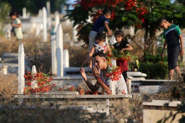 فلسطین کے شہر غزہ میں عید الفطر کی نماز کے بعد ایک شخص قبر پر دعا کرتا ہوا ۔