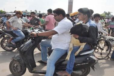 لکھنو میں ایک شخص موٹر سائیکل پر بکرا خرید کر لے جاتے ہوئے۔
