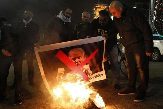 امریکی صدر ٹرمپ کی تصاویر کور نذر آتش کرکے احتجاج کیا گیا ہے۔