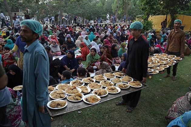 لاہور میں مفت کھانا ڈسٹربیوشن سینٹر میں لوگوں کے روزہ کھولنے کے دوران کھانا تقسیم کرنے کی تصویریں۔