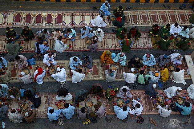 پاکستان کے کراچی شہر میں سڑک کنارے روزہ کھولنے کا انتظار کرتے لوگوں کی تصویر