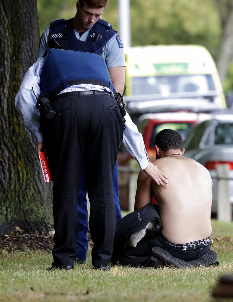 سینٹرل کرائسٹ چرچ میں ایک آدمی کو دلاسہ دیتے ہوئے پولیس اہلکار ۔( فوٹو : اے پی ) ۔