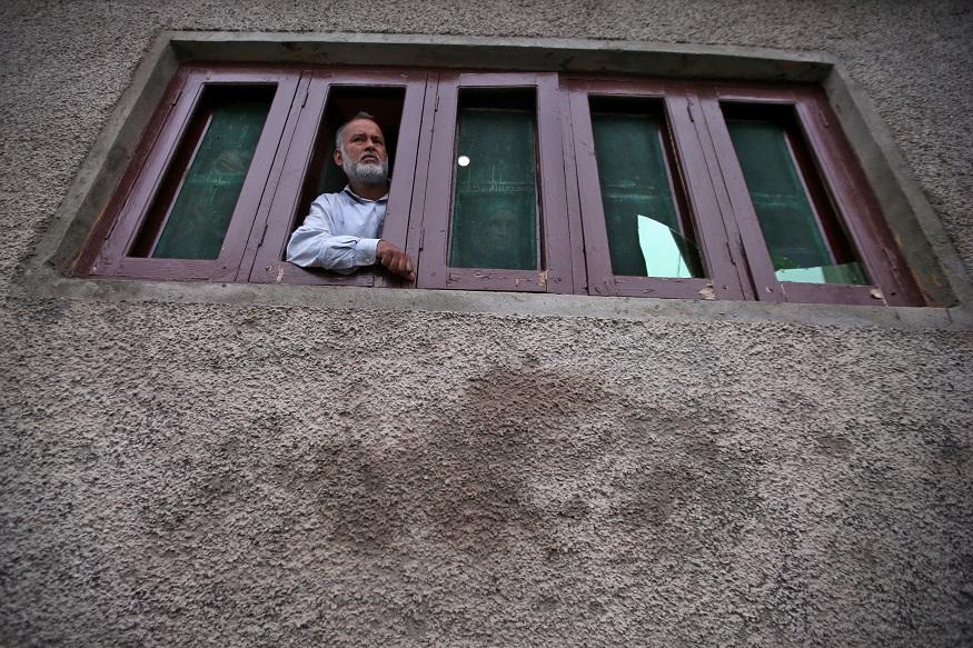 ایک کشمیری شہری اپنے مکان میں باہر کا نظارہ کرتے ہوئے۔(تصویر:رائٹرز)۔