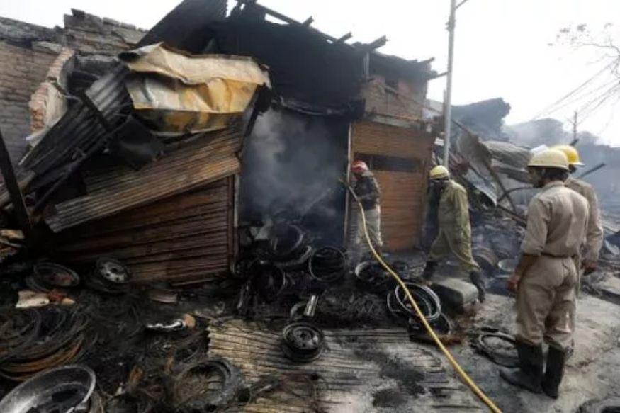 دہلی تشدد کے دوران لی گئی تصویر میں پولیس ایک دکان میں لگائی گئی آگ پرقابوپاتے ہوئے۔(تصویر:نیوز18)۔